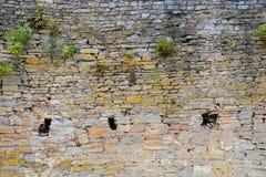 Beschaffenheit der alten mittelalterlichen Schlosswand mit dem Schlupfloch gemacht von den grauen Steinen Stockfotos