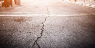 Beschaffenheit der alten Straße mit Sprüngen Asphaltoberfläche auf der Straße Greller Glanz des Lichtes Netzfahnengröße 16 in Ern Stockfoto