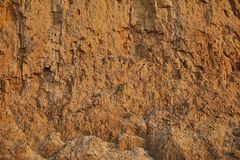 Beschaffenheit der Lehmsandwand der roten Farbe mit vielen Sprüngen der unterschiedlichen Tiefe stockfoto
