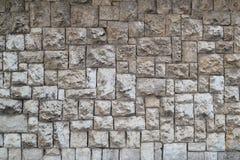 Beschaffenheit der Wand hergestellt von den Steinblöcken von verschiedenen Größen und von hellgrauer Farbe Stockbild