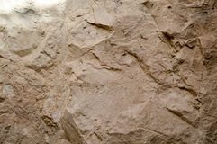 Beschaffenheit der Wand wird vom gelben sandigen bröckeligen Felsen des Felsens mit Scherben und Schichten gemacht Der Hintergrun Stockfotografie