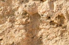 Beschaffenheit der Wand wird vom gelben sandigen zerreibbaren alten faulen Stein des Felsens mit Scherben, Löchern und Schichten  Lizenzfreie Stockfotografie