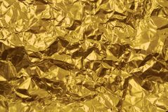 Beschaffenheit der zerknitterten goldenen gelben Folie mit Einbuchtungsnahaufnahme stockbild