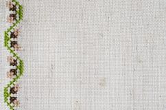 Beschaffenheit des beige Leinengewebes mit Stickerei lizenzfreie stockfotografie