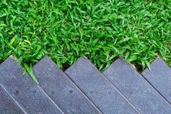 Beschaffenheit des grünen Grases mit Holzfußboden Stockfotografie
