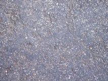 Beschaffenheit des rauen Asphalts, der dunkelgrauen Straße mit kleinem Felsen und des cra Stockbild