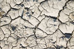 Beschaffenheit des trockenen gebrochenen grauen Lehms mit Sonnenblende lizenzfreie stockfotografie