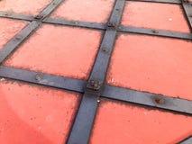 Beschaffenheit einer alten alten mittelalterlichen roten antiken starken Eisenmetalltür mit Nieten und Nagelmustern Der Hintergru lizenzfreie stockfotografie