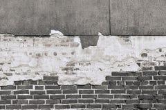 Beschaffenheit einer alten schwarzen Backsteinmauer mit zerstörtem Gips Stockbild