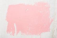 Beschaffenheit einer alten ungleichen weißen Wand mit einer abstrakten Stelle der rosa Farbe, gemalt mit einer Bürste unter Verwe Stockfotos