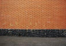 Beschaffenheit einer Wand des roten Backsteins mit einer schwarzen Basis des wilden Steins und Lizenzfreies Stockfoto