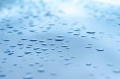 Beschaffenheit eines Wassertropfens auf einer blauen glatten Oberfläche Stockfotografie