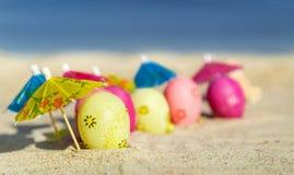 Beschaffenheit (Hintergrund) mit bunten Ostereiern mit Regenschirmen auf dem Strand mit Meer Stockfoto