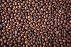 Beschaffenheit und Hintergrund von den Röstkaffeebohnen auf dem Tisch zerstreut stockbild