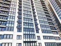 Beschaffenheit von blauen widergespiegelten Fenstern und von Balkonen eines hohen modernen Monolithischrahmengebäudes, Haus, Neub stockfotografie