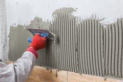 Beschaffenheit von ceranic Tilerman-Hand, die klebendes Material verbreitet Lizenzfreie Stockbilder