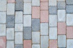 Beschaffenheit von Pflastersteinen des grauen rechteckigen konkreten Steins auf der Straße mit Nähten Der Hintergrund lizenzfreie stockfotos
