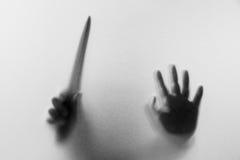 Beschatten Sie Hände mit Messer des Mannes hinter Mattglas Undeutliches h Stockfoto