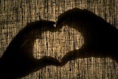 Beschatten Sie Hände und Finger in Form eines Herzens auf Leinensegeltuch Lizenzfreies Stockbild