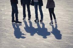 Beschatten Sie Hintergrund der Gruppe Jugendlicher auf dem Eis Stockbilder