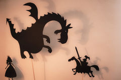 Beschatten Sie Marionetten des Drachen, der Prinzessin und des Ritters mit hellem glühendem Schirm des Schattentheaters im Hinter Lizenzfreie Stockbilder