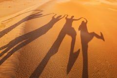 Beschatten Sie Schattenbilder von vier Leuten in der Wüste Stockfotos