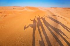 Beschatten Sie Schattenbilder von vier Leuten in der Wüste Stockbilder