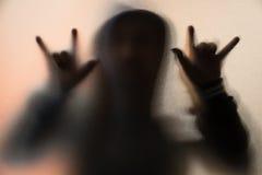 Beschatten Sie Unschärfe des Horrormannes in der Jacke mit Haube Finger tun als sym Lizenzfreie Stockfotos