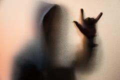Beschatten Sie Unschärfe des Horrormannes in der Jacke mit Haube Finger tun als sym Lizenzfreies Stockfoto