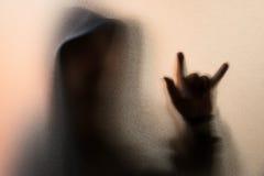 Beschatten Sie Unschärfe des Horrormannes in der Jacke mit Haube Finger tun als sym Stockfotografie