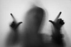 Beschatten Sie Unschärfe des Horrormannes in der Jacke mit Haube Hände auf dem Glas Lizenzfreies Stockfoto