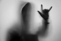 Beschatten Sie Unschärfe des Horrormannes in der Jacke mit Haube Hände tun als symb Stockbilder