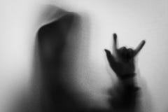 Beschatten Sie Unschärfe des Horrormannes in der Jacke mit Haube Hände tun als symb Stockbild
