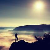 Beschattende Augen des Mannes Alleintourist auf Klippenrand und Aufpassen in tiefes Tal Stockfoto