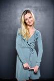 Bescheidenes blondes Mädchen auf einem grauen Wandhintergrund Stockbild