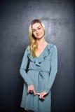 Bescheidenes blondes Mädchen auf einem grauen Wandhintergrund Lizenzfreies Stockbild