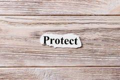 Bescherm van het woord op papier Concept Woorden van Protect op een houten achtergrond royalty-vrije stock foto