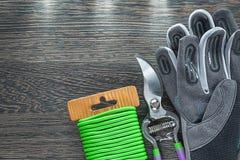 Beschermende de tuindraad van de handschoenensnoeischaar op houten raad Stock Afbeeldingen