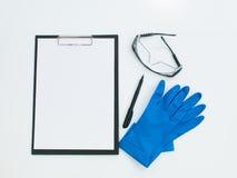 Beschermende laboratoriumtoebehoren met pen en klembord Royalty-vrije Stock Afbeelding