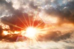 beschäftigte dunkle Wolke über vibrierendem Farbhimmel mit rotem sunstar Aufflackern Stockbilder