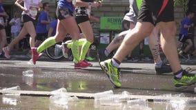 Beschikbaar koppen en water onder de voeten het runnen van marathonagenten stock footage