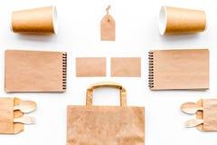 Beschikbaar vaatwerk Document kop, lepel, vork dichtbij pakpapierzak en spot van de notitieboekje de hoogste mening op patroon wi stock fotografie