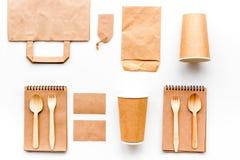 Beschikbaar vaatwerk Document kop, lepel, vork dichtbij pakpapierzak, etiket en spot van de notitieboekje de hoogste mening op pa royalty-vrije stock afbeeldingen
