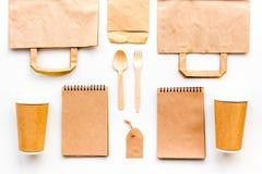 Beschikbaar vaatwerk Document kop, lepel, vork dichtbij pakpapierzak, etiket en spot van de notitieboekje de hoogste mening op pa royalty-vrije stock afbeelding
