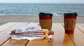 Beschikbare koppen die van koffie zich op een lijst tegen het blauwe overzees bevinden Koffiekop op Houten lijstbovenkant op het  stock afbeeldingen