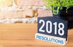 Beschlüsse des neuen Jahres 2018 auf Tafelzeichen und Grünpflanze an Stockfotos