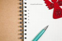 Beschlüsse des neuen Jahres, Notizbuch und grüner Stift mit hölzernem Rot-ANG Stockbilder