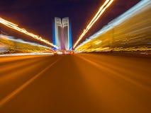 Beschleunigen Sie Bewegung auf der glühenden Neonstraße an der Dunkelheit Stockfotografie
