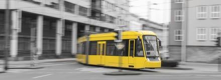beschleunigende gelbe Tram mit Schwarzweiss-Stadthintergrund Lizenzfreie Stockfotografie