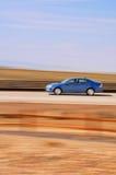 Beschleunigendes blaues Auto mit unscharfem Hintergrund Stockfoto